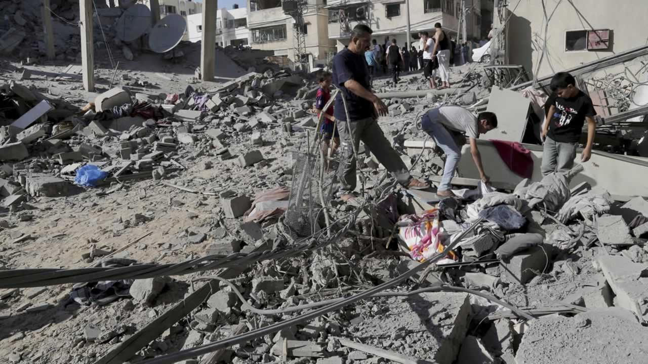 Palestinians salvage what they can of their family belongings from the rubble of a four-story building following an Israeli air strike.