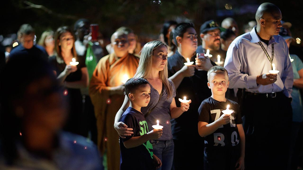People attend a candlelight memorial for Las Vegas police officer Charleston Hartfield, Thursday, Oct. 5, 2017, in Las Vegas.
