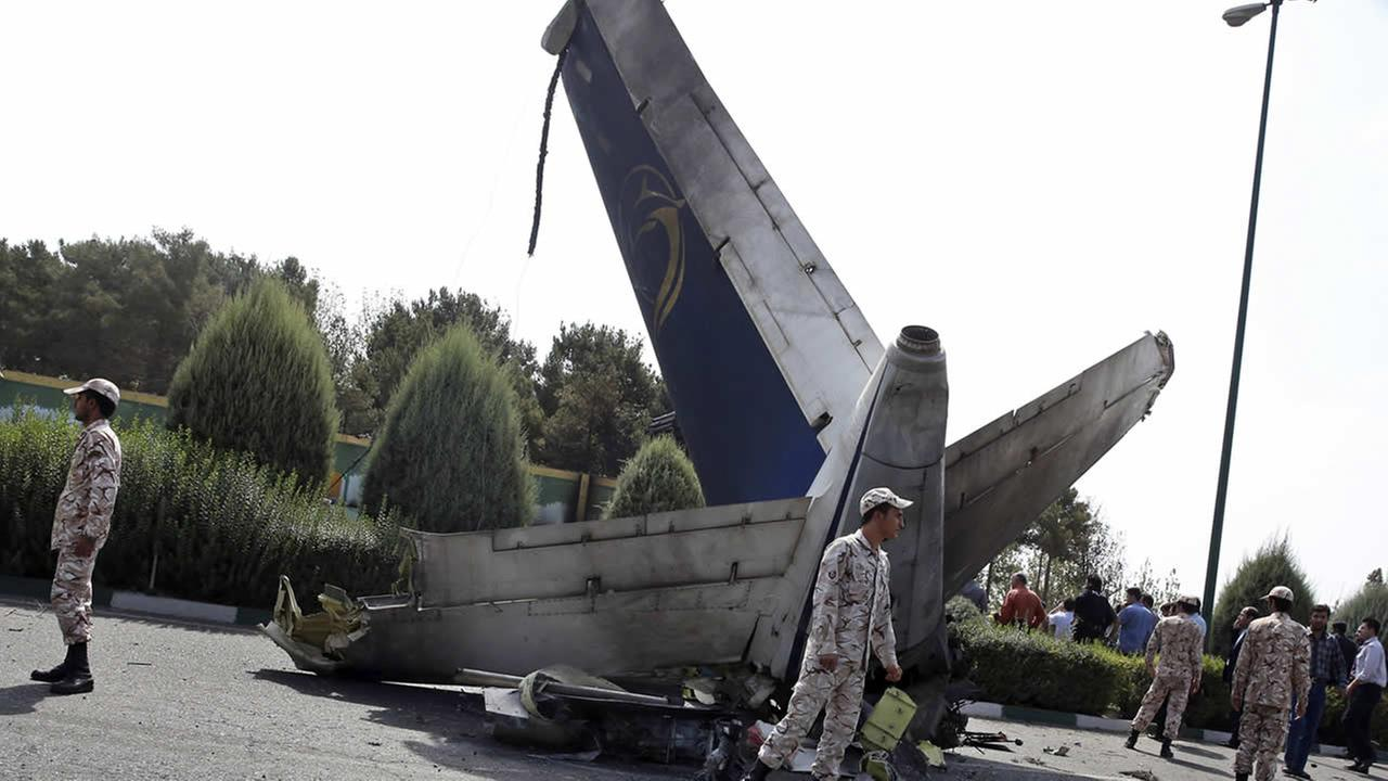 Iranian Revolutionary Guard soldiers surround the wreckage of a passenger plane which crashed while taking off from the capital, Tehran, Iran, Sunday, Aug. 10, 2014. (AP Photo/Vahid Salemi)