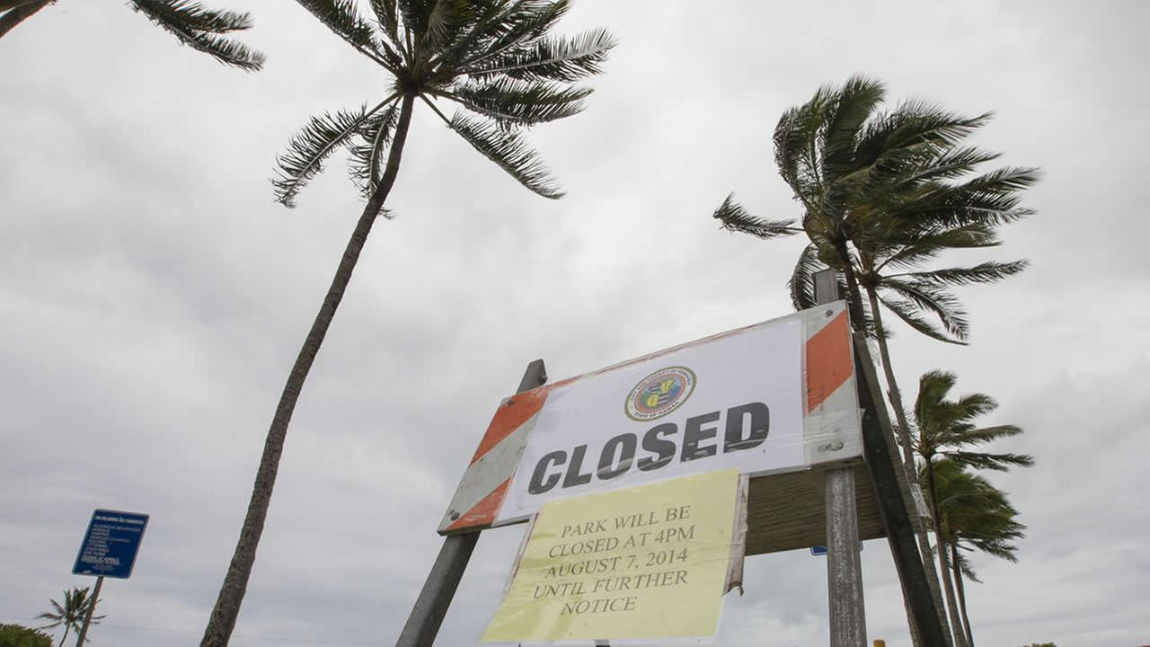 Winds from Tropical Storm Iselle blow palm trees near a sign warning of the closure of Kualoa Regional Park in Honolulu on Friday, Aug. 8, 2014. (AP Photo/Eugene Tanner)