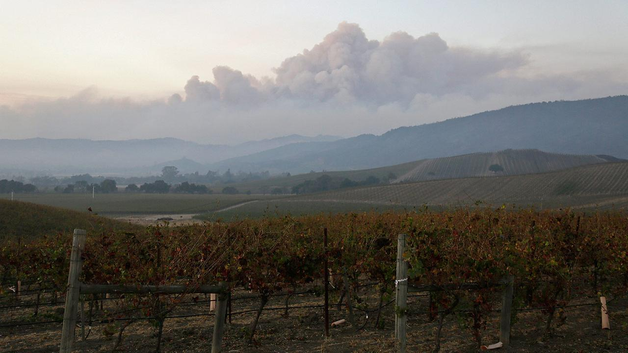 Smoke from wildfires in the Sonoma Valley makes its way toward the Napa Valley, in this view from the Carneros wine region, Tuesday, Oct. 10, 2017, in Napa, Calif.