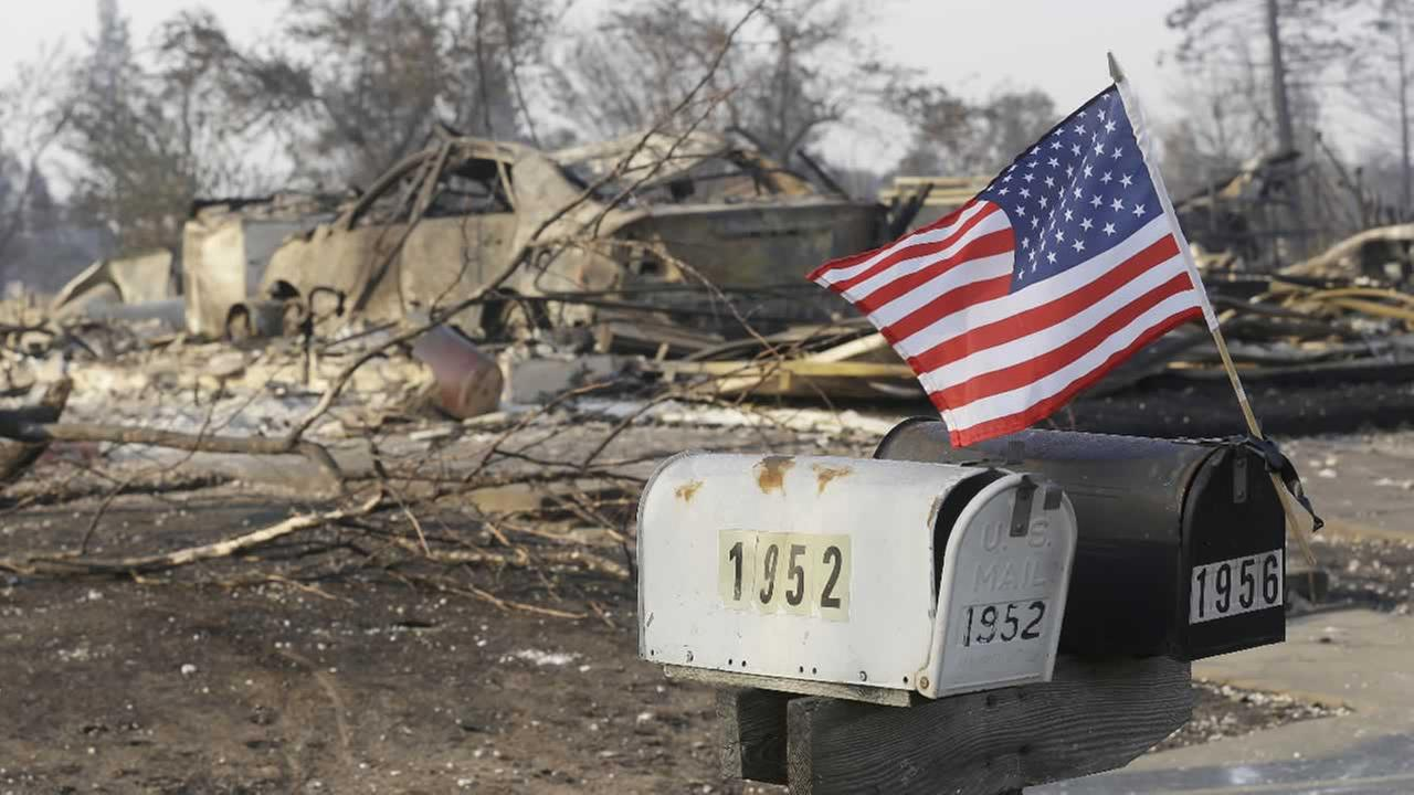 A small flag attached to mail boxes flies in front of homes destroyed by fires in Santa Rosa, Calif., Wednesday, Oct. 11, 2017.