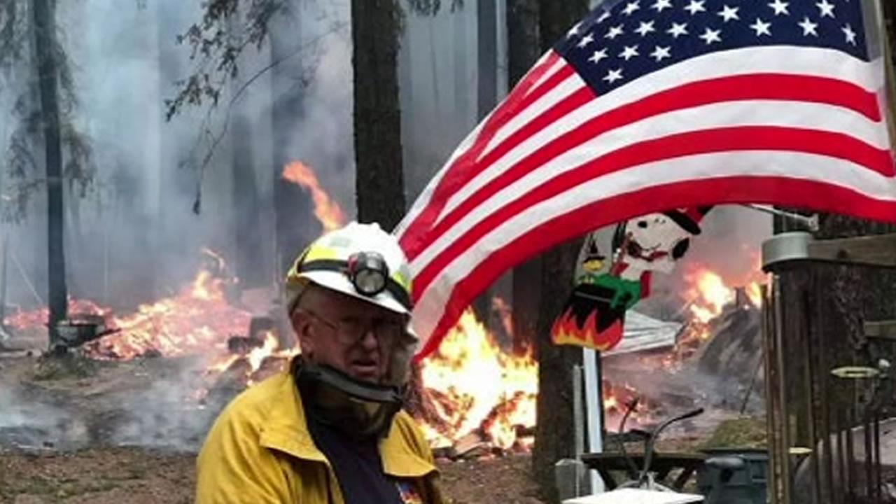 Will Horne, 79, stands near an American flag as flames billow in the background during the North Bay Fires in Santa Rosa, Calif. on Friday, Oct. 13, 2017.