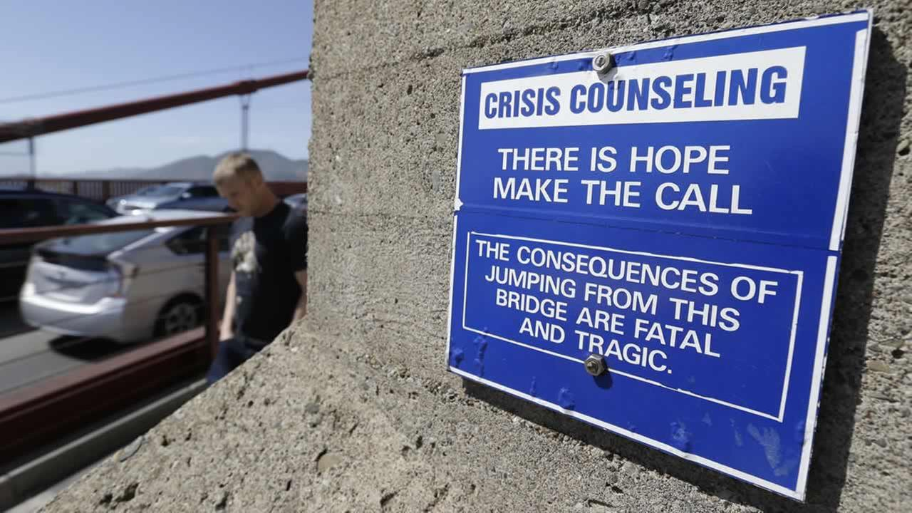 A sign is posted above a crisis counseling call box on the Golden Gate Bridge in San Francisco. (AP Photo/Eric Risberg)