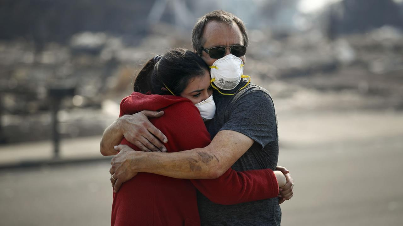 Howard Lasker, right, comforts his daughter, Gabrielle, who is visiting their home for the first time since a wildfire swept through it Sunday, Oct. 15, 2017, in Santa Rosa, Calif.