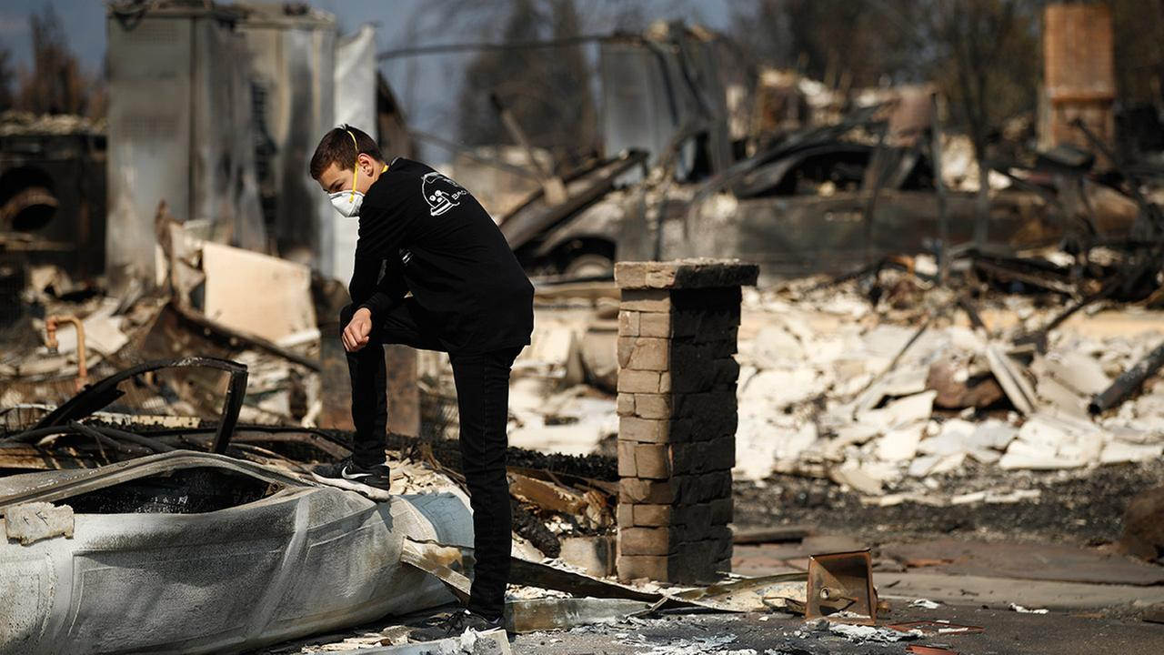 Benjamin Lasker, 16, pauses while looking at what remains of his home after a wildfire swept through Sunday, Oct. 15, 2017, in Santa Rosa, Calif.