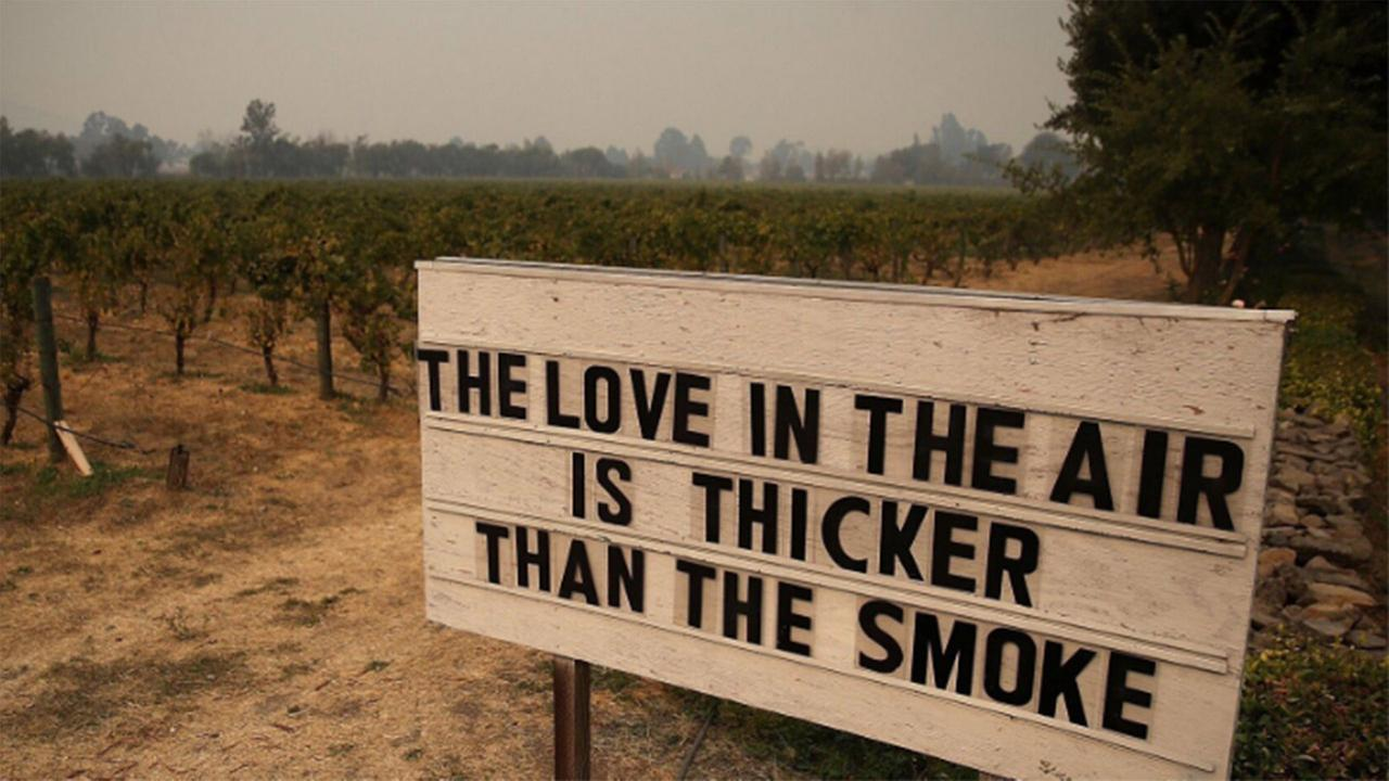 FILE -- Sign with the statement the love in the air is thicker than the smoke in Sonoma, California.