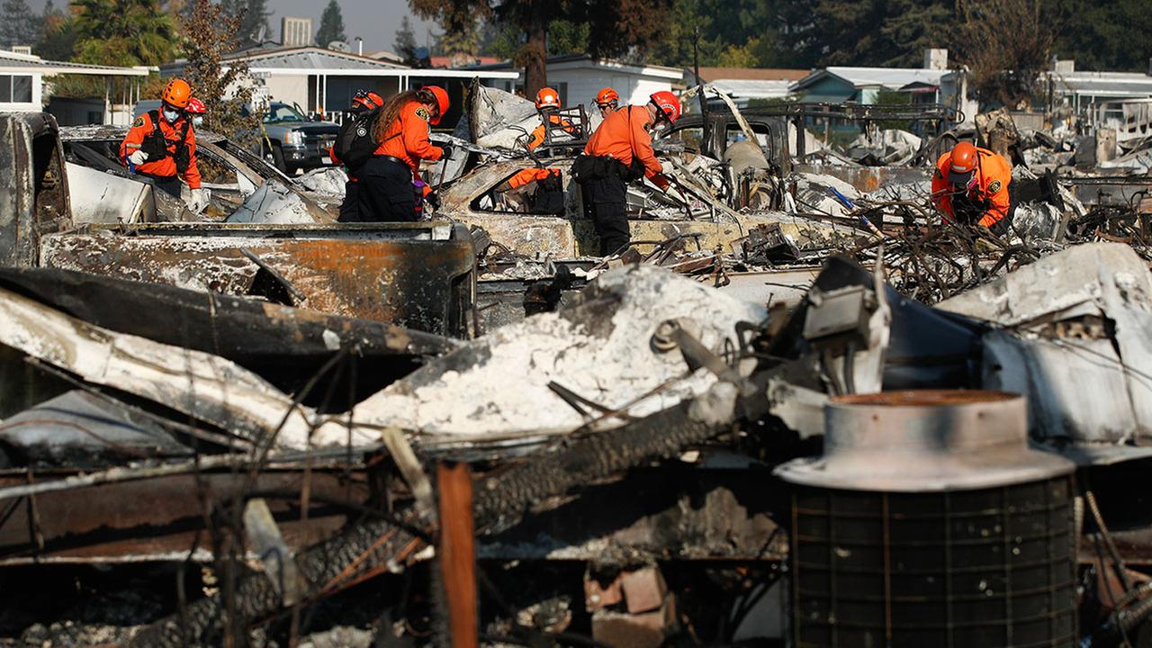 Members of a search and rescue team search through the rubble of mobile homes destroyed by a wildfire Monday, Oct. 16, 2017, in Santa Rosa, Calif.