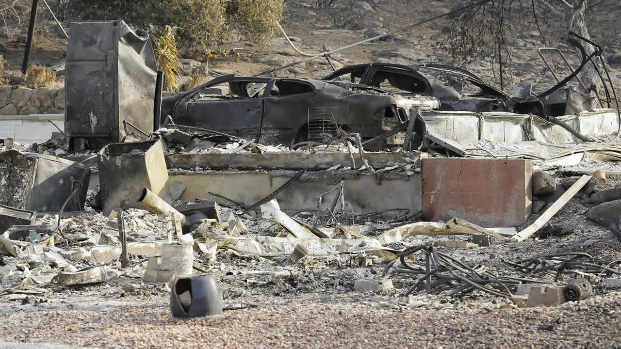 Two cars are among the remains Monday, Oct. 16, 2017, at the house where Sara and Charles Rippey died a week ago in a fast-moving wildfire in Napa, Calif. (AP Photo/Eric Risberg)