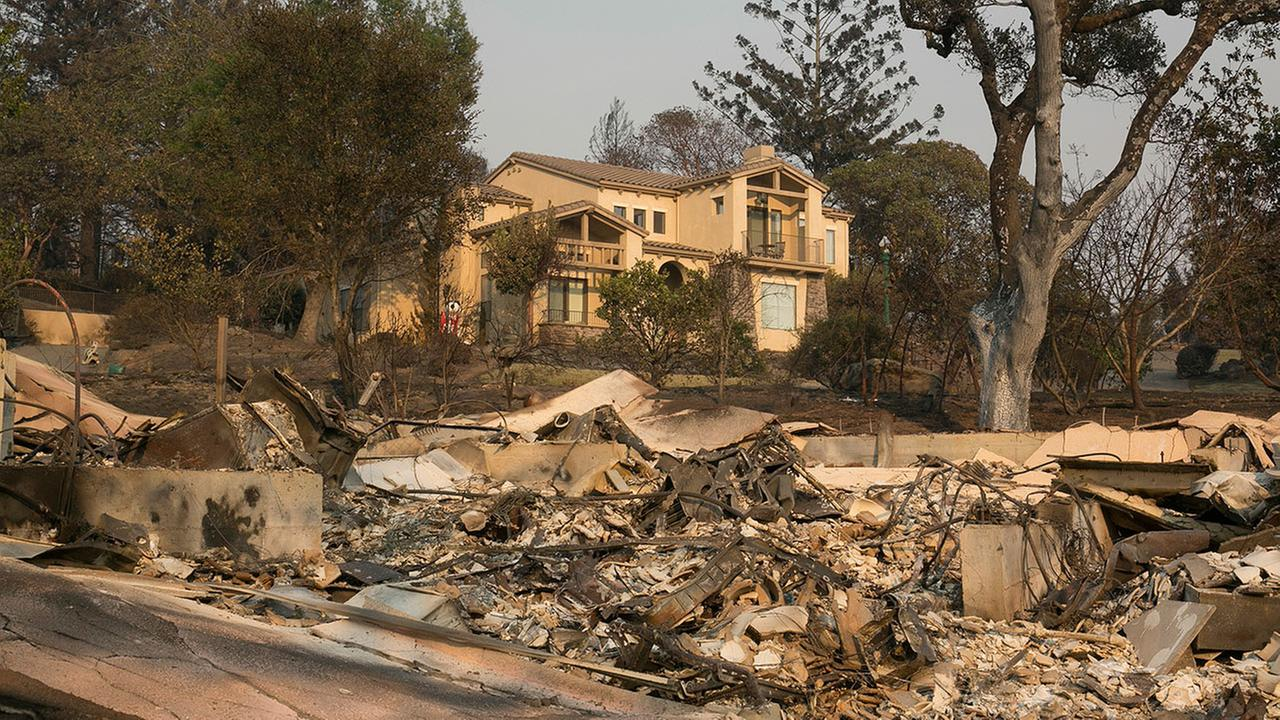 A large home that survived last weeks wildfire sits by the burned ruins of a nearby home, Monday, Oct. 16, 2017, in Santa Rosa, Calif.