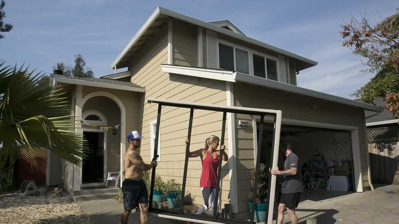 Chris Alejos, left, and his wife get help from friend Nick Cann as they remove a bed frame from their home in the Coffey Park area of Santa Rosa, Calif. Monday, Oct. 16, 2017.