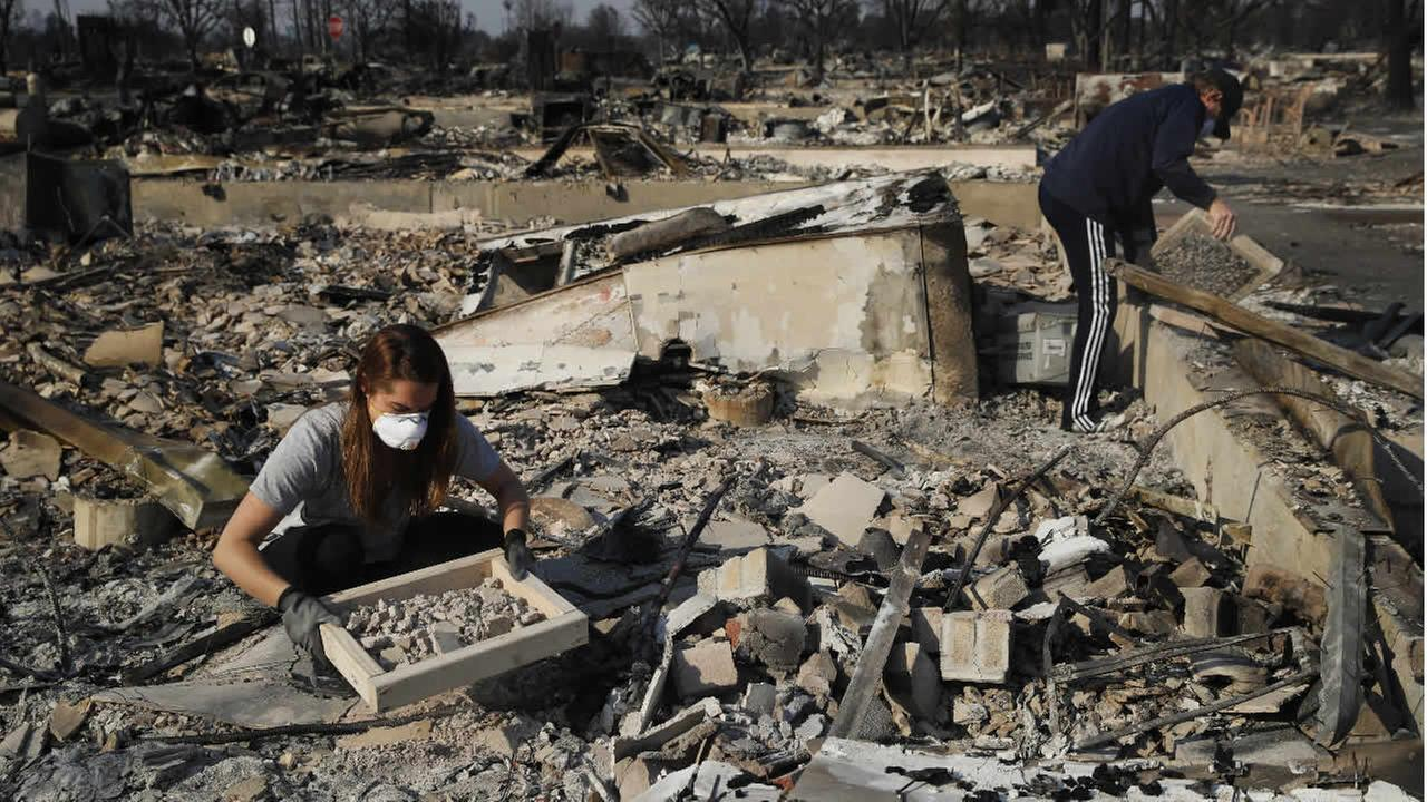 Residents search through rubble of their home destroyed by a wildfire in the Coffey Park neighborhood Sunday, Oct. 15, 2017, in Santa Rosa, Calif.