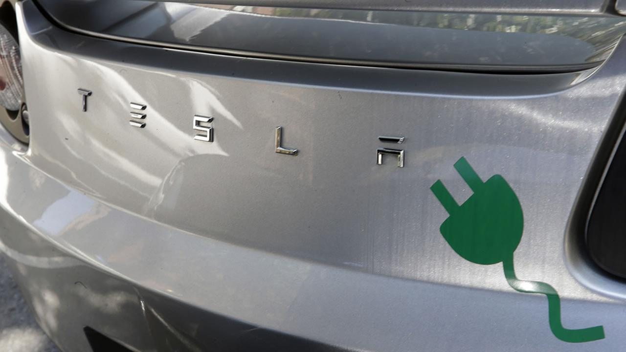 An electric plug decal is seen on the back of a Tesla electric car, Monday, June 16, 2014, in Trenton, N.J. (AP Photo/Mel Evans)