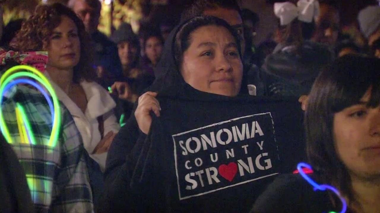A woman wears a sweatshirt that reads SONOMA COUNTY STRONG at a vigil for fire victims in Santa Rosa, Calif. on Friday, Oct. 20, 2017.