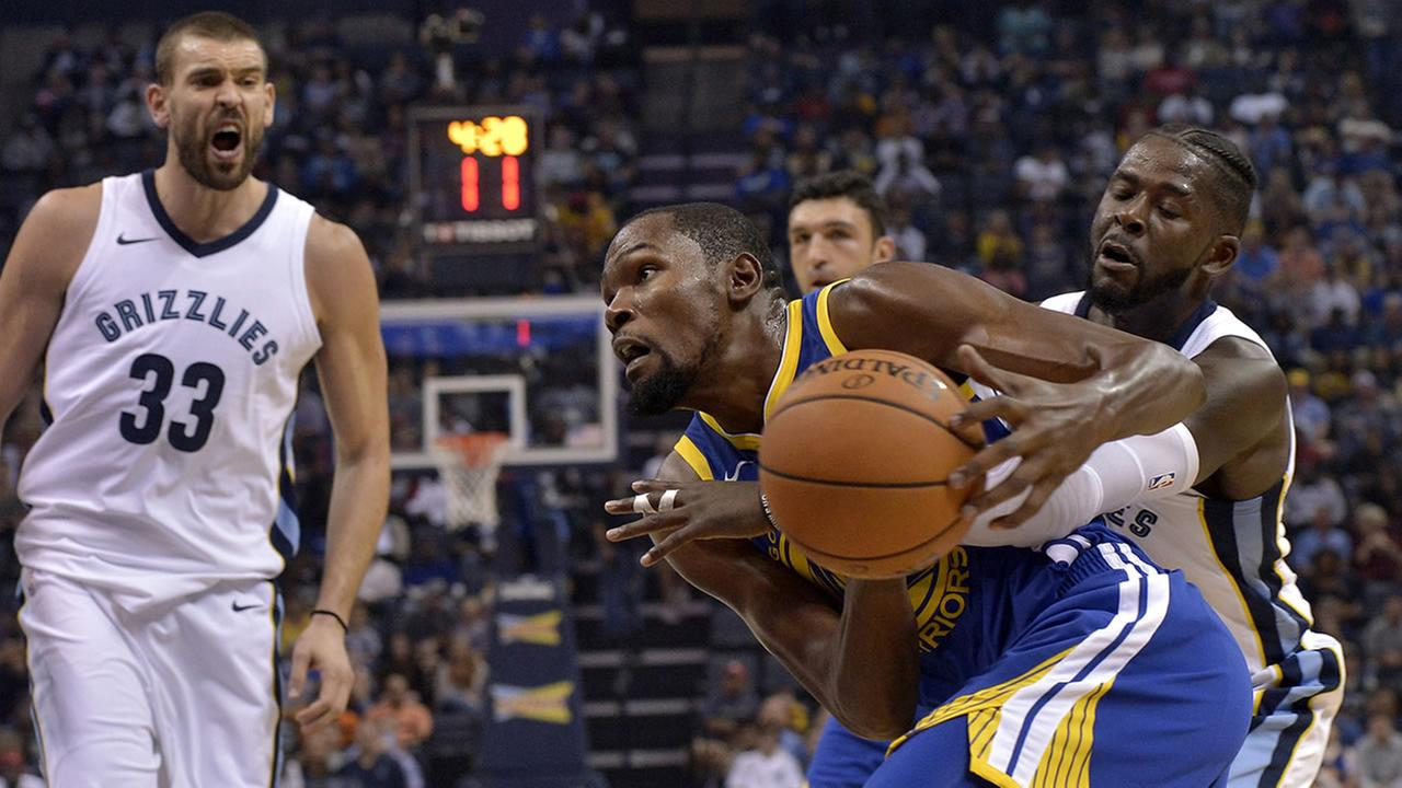 Golden State Warriors forward Kevin Durant, center, drives against Memphis Grizzlies forward James Ennis III, right, during the first half of an NBA basketball game Saturday, Oct. 21, 2017, in Memphis, Tenn. (AP Photo/Brandon Dill)