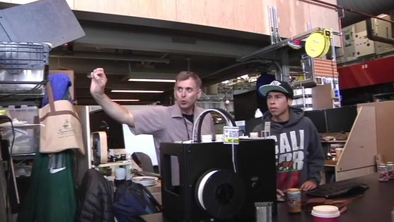 An Exploratorium employee instructs a student from the Boys and Girls Club.