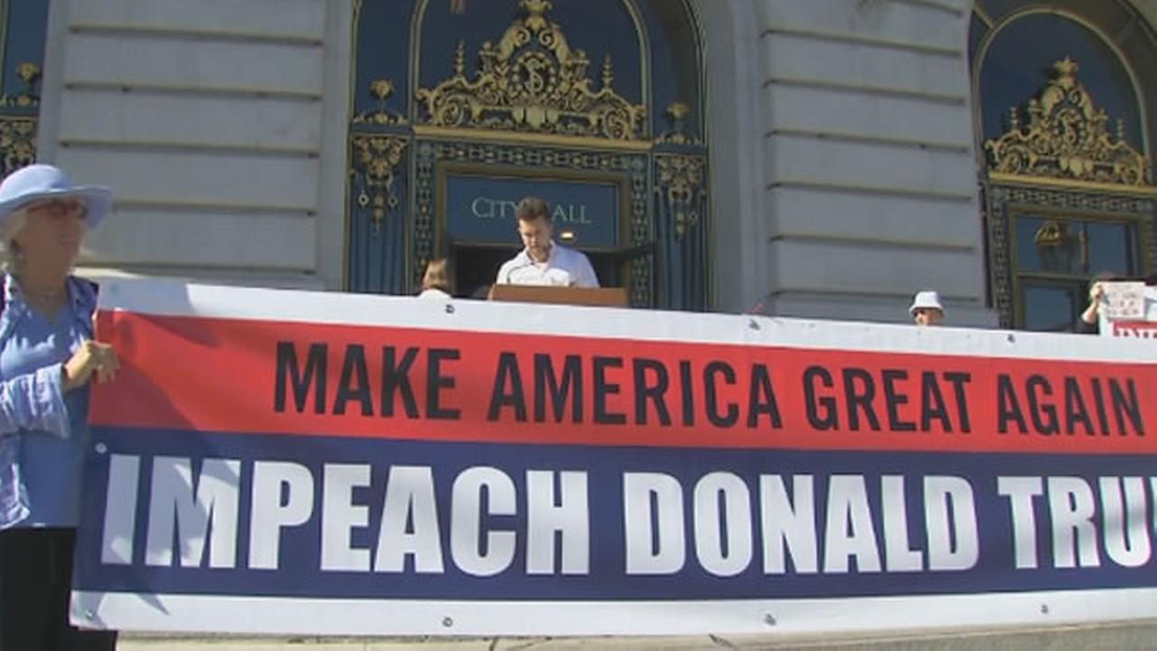 A demonstrator holds a banner that reads Make America Great Again. Impeach Donald Trump.