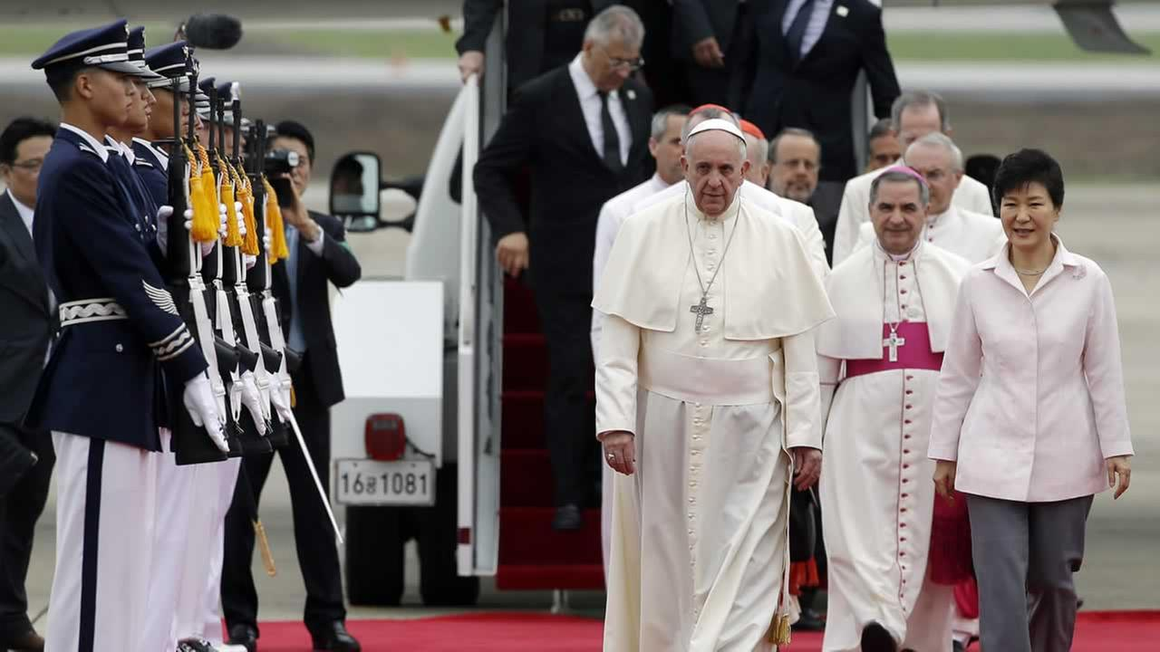 Pope Francis walks with South Korean President Park Geun-hye upon his arrival in Seoul, Thursday, Aug. 14, 2014.