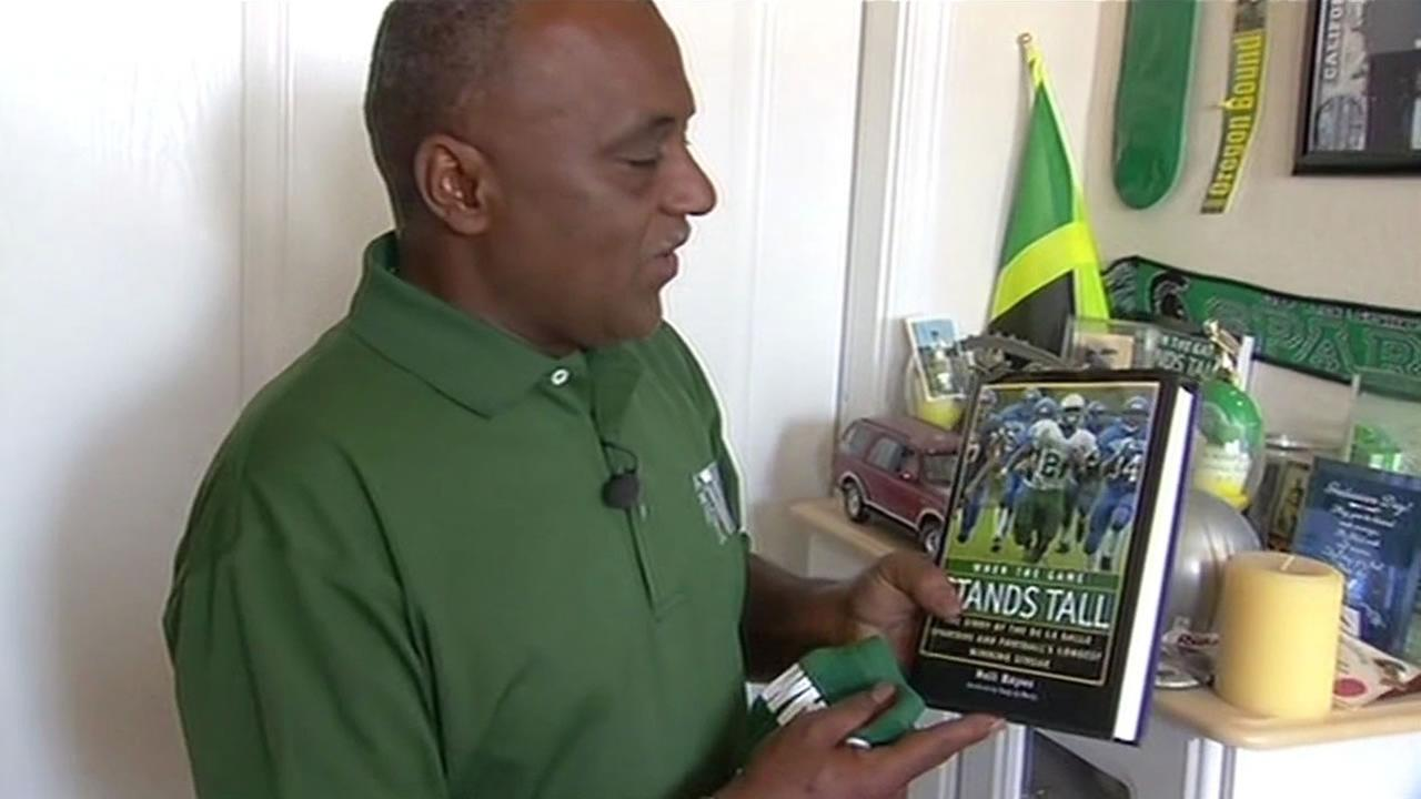 Landrin Kelly holding up a copy of the book, When the Game Stands Tall.