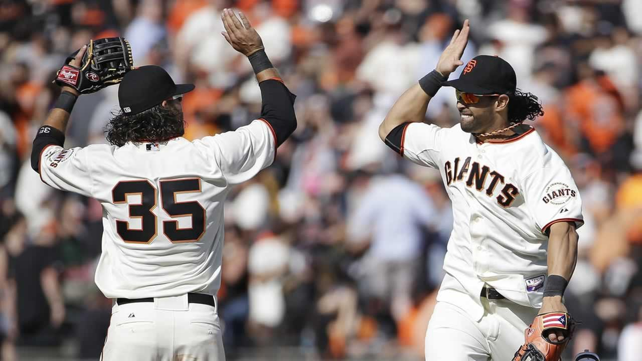 San Francisco Giants shortstop Brandon Crawford, left, greets center fielder Angel Pagan, right, at the end of of the home opener MLB National League baseball game against the Arizona Diamondbacks in San Francisco, Tuesday, April 8, 2014. San Francisco won the game 7-3. (AP Photo/Eric Risberg)