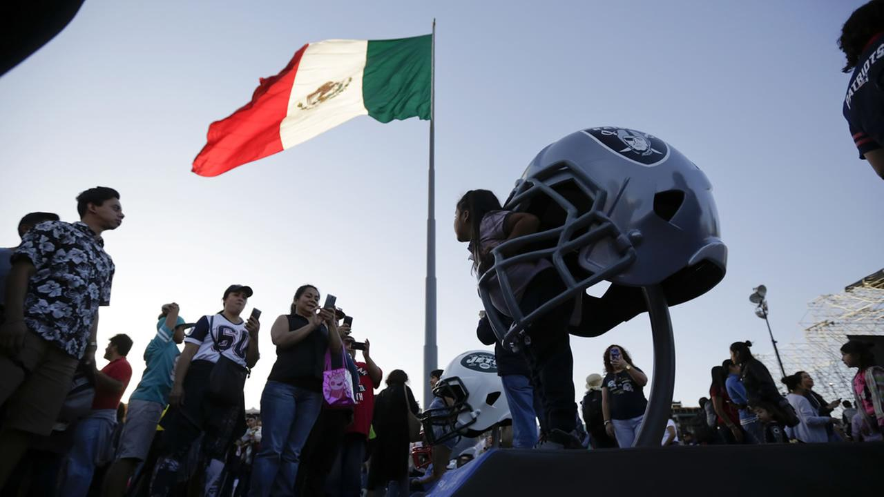 A girl poses inside a giant Oakland Raiders helmet during NFL footballs Fan Fest in Mexico Citys main square, the Zocalo, Saturday, Nov. 18, 2017.