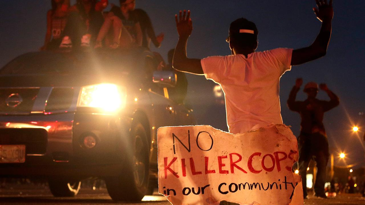 People protest Sunday, Aug. 17, 2014, for Michael Brown, who was killed by a police officer last Saturday in Ferguson, Mo.