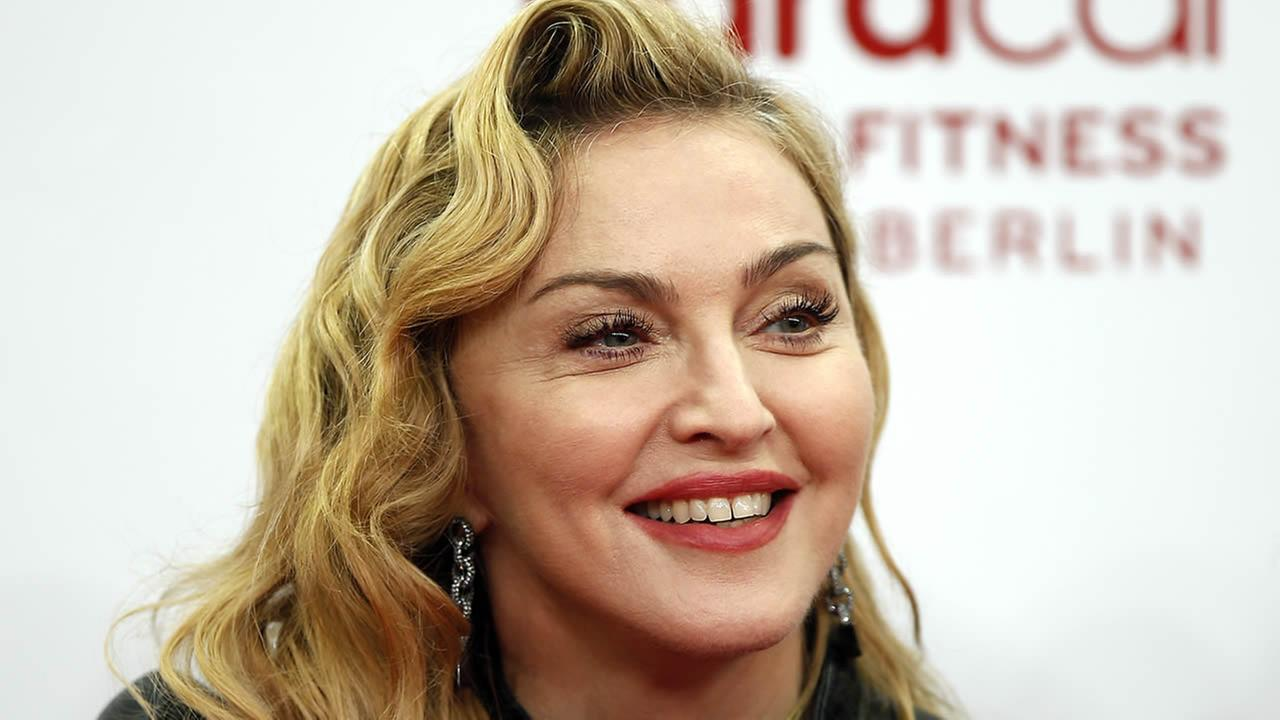 In this Oct. 17, 2013, file photo, U.S. pop star Madonna smiles during her visit at the Hard Candy Fitness center in Berlin. (AP Photo/Michael Sohn, File)