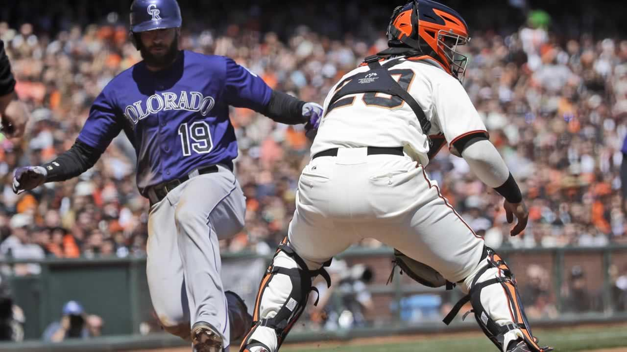 Colorado Rockies Charlie Blackmon (19) scores past San Francisco Giants catcher Hector Sanchez, right, on a sacrifice fly hit by Troy Tulowitzki during the third inning of a baseball game on Saturday, April 12, 2014, in San Francisco. (AP Photo/Marcio Jose Sanchez)