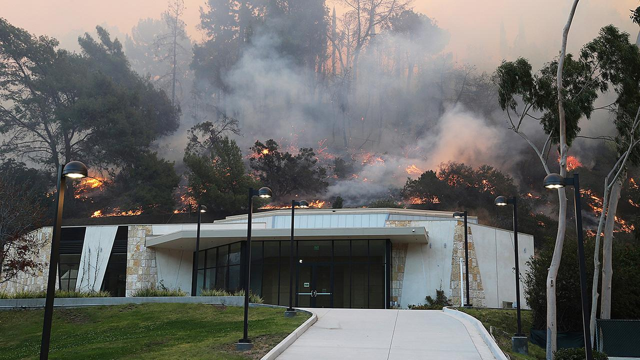 Flames from a wildfire work their way down a slope behind Leo Baeck Temple in Sepulveda Pass in the Bel Air district of Los Angeles Wednesday, Dec. 6, 2017.