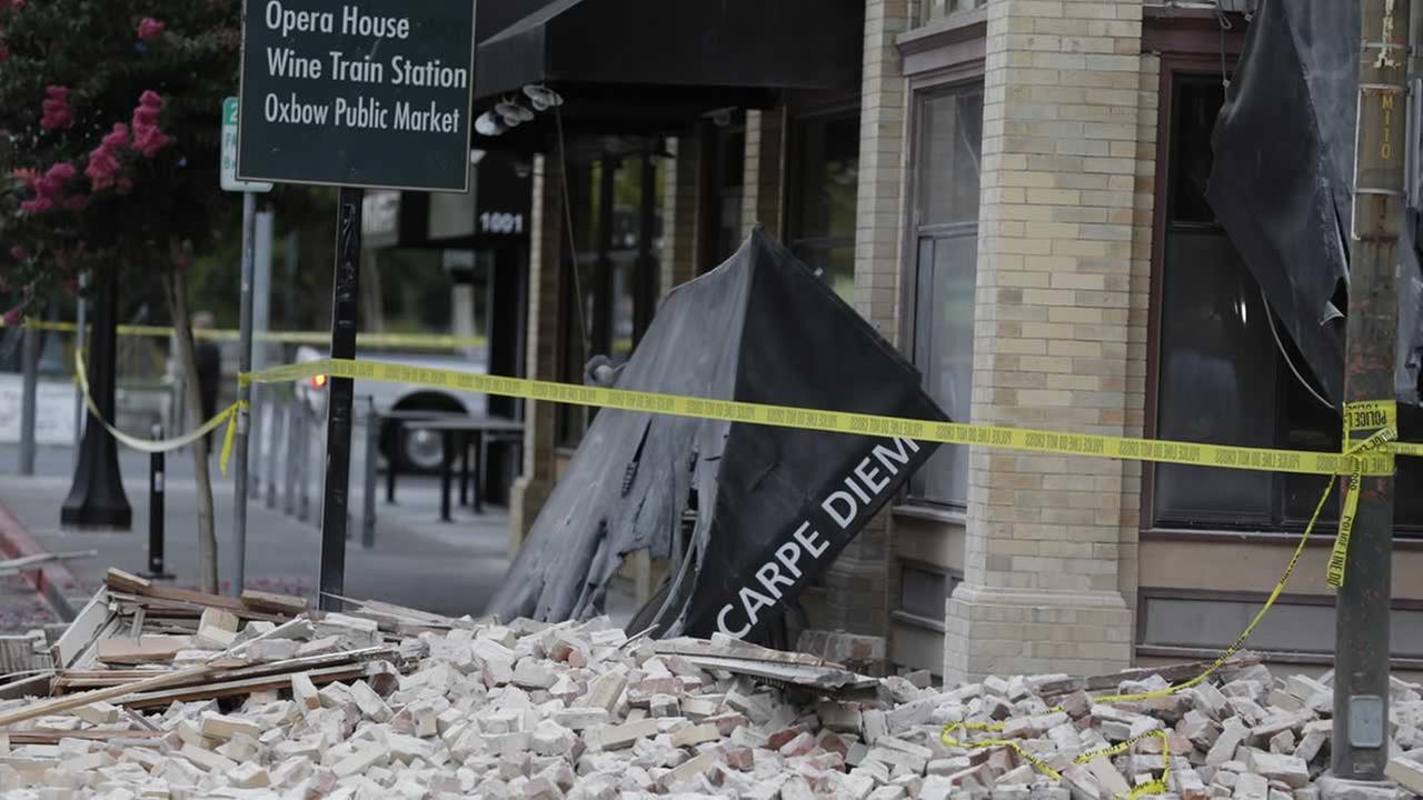 Bricks and rubble cover the sidewalk in front of a heavily damaged building following an earthquake Sunday, Aug. 24, 2014, in Napa, Calif. (AP Photo/Eric Risberg)