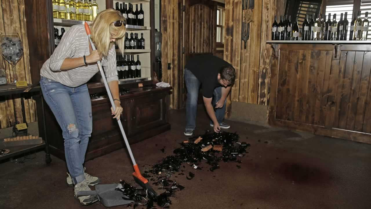 Janelle Dahl and her son Austin clean up broken bottles of wine in a tasting room after an earthquake at Dahl Vineyards Sunday, Aug. 24, 2014, in Yountville, Calif. (AP Photo/Eric Risberg)