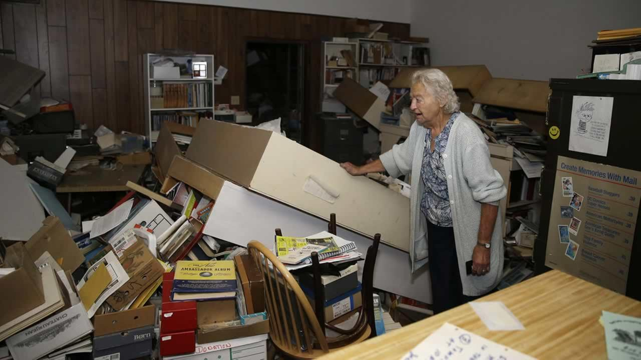 Jean Meehan looks over the damage to her JHM Stamp and Collectibles store following an earthquake Sunday, Aug. 24, 2014, in Napa, Calif. (AP Photo/Eric Risberg)
