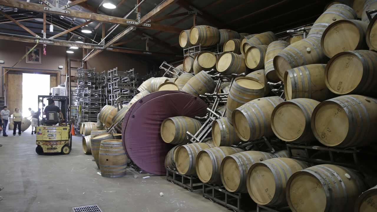 Cellar workers continue cleanup after a number of barrels toppled following an earthquake at the Saintsbury winery Sunday, Aug. 24, 2014, in Napa, Calif.  (AP Photo/Eric Risberg)
