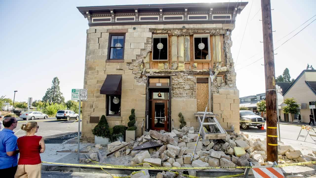 Pedestrians stop to examine a crumbling facade at the Vintners Collective tasting room in Napa, Calif., following an earthquake Sunday, Aug. 24, 2014. (AP Photo/Noah Berger)