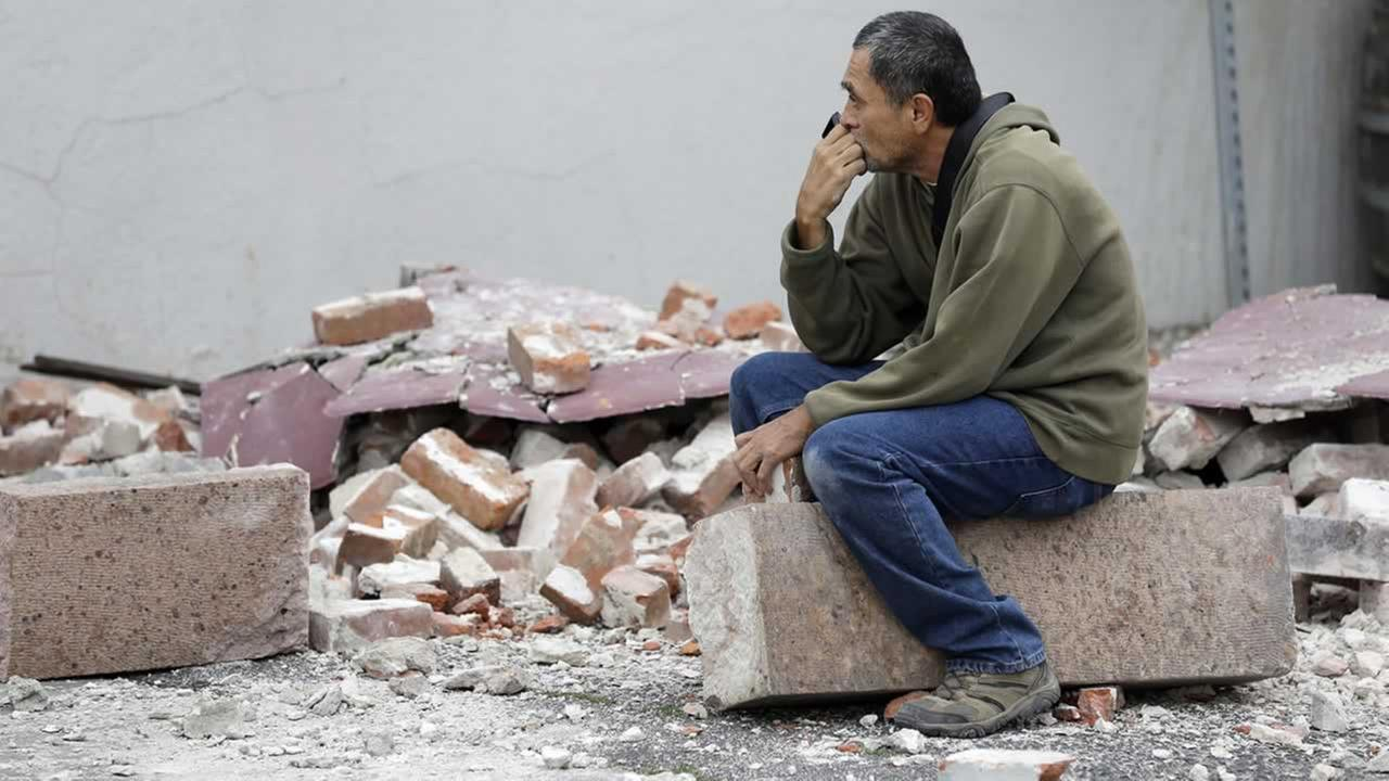 Ron Peralez, of Vacaville, Calif., sits on rubble and looks at earthquake-damaged buildings Monday, Aug. 25, 2014, in Napa, Calif. (AP Photo/Eric Risberg)
