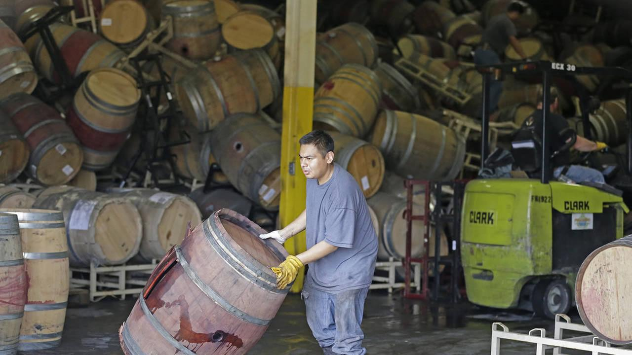 A worker removes an earthquake-damaged wine barrel from a barrel storage facility Monday, Aug. 25, 2014, in Napa, Calif.AP Photo/Eric Risberg