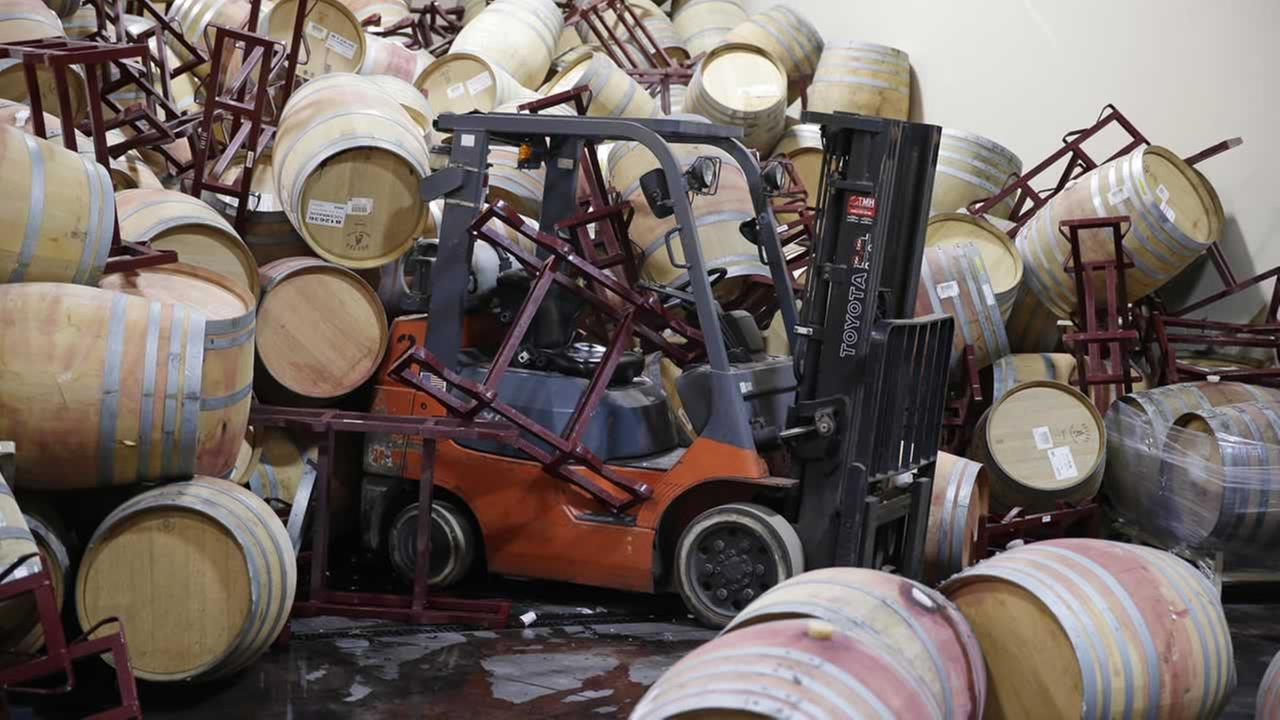 A forklift is partially buried in some of the hundreds of earthquake damaged wine barrels at the Kieu Hoang Winery Monday, Aug. 25, 2014, in Napa, Calif. (AP Photo/Eric Risberg)