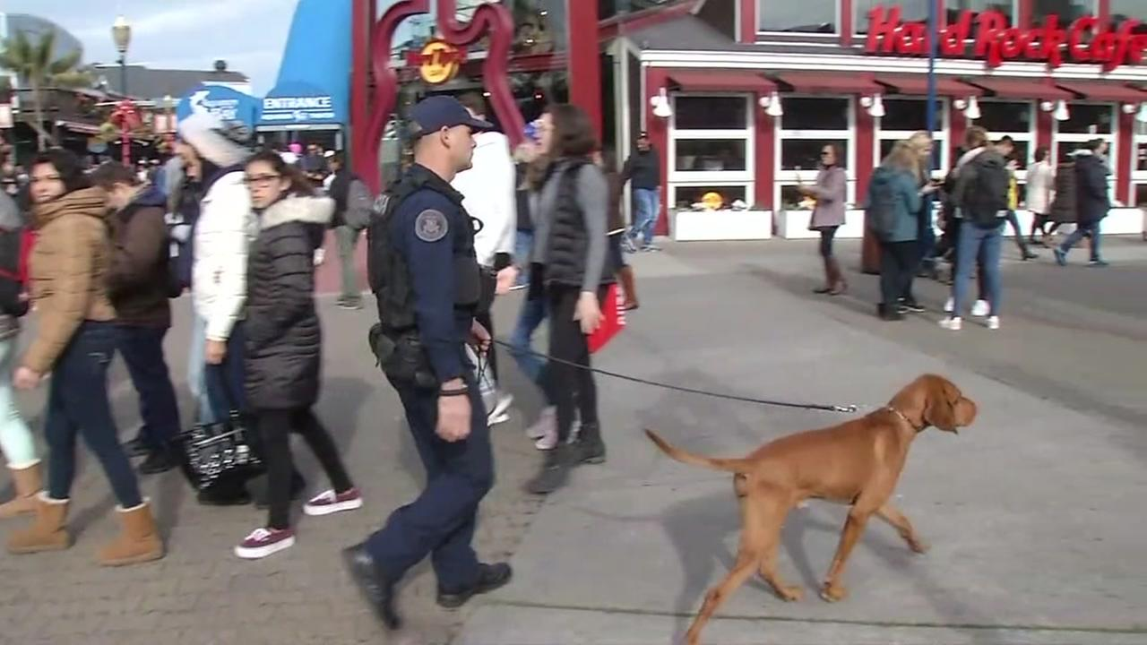 A police officer is seen with a dog at San Franciscos Pier 39 on Saturday, Dec. 23, 2017.