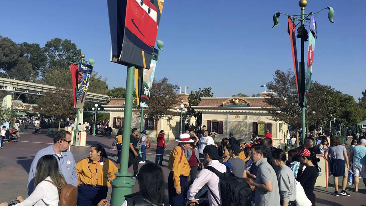 In this photo provided by Dan Greenspan, workers stop people from approaching Disneylands entrance as the turnstiles are roped off at the park in Anaheim, Calif. on Dec. 27, 2017.