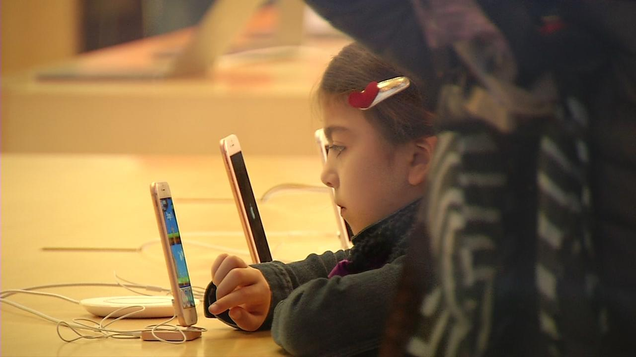 A child examines an iPhone in this undated image.