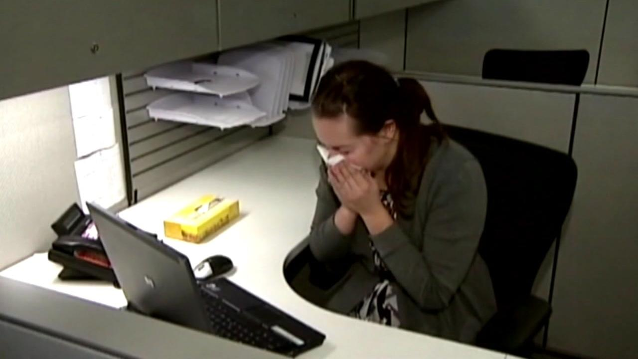 This is an undated image of a woman sneezing at her desk.