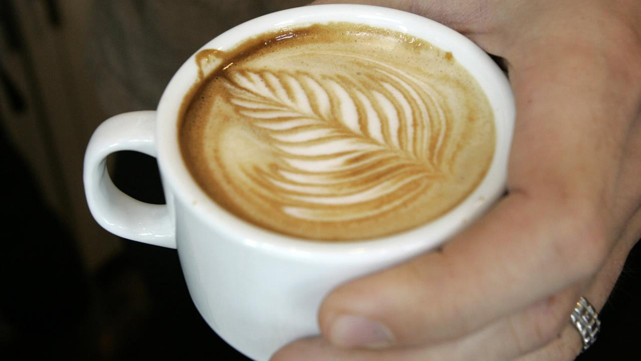 Luke Shaffer shows his signature leaf design on the top of a latte in his 21st Street coffee and tea shop in Pittsburghs Strip District on May 21, 2008 (AP Photo/Keith Srakocic)