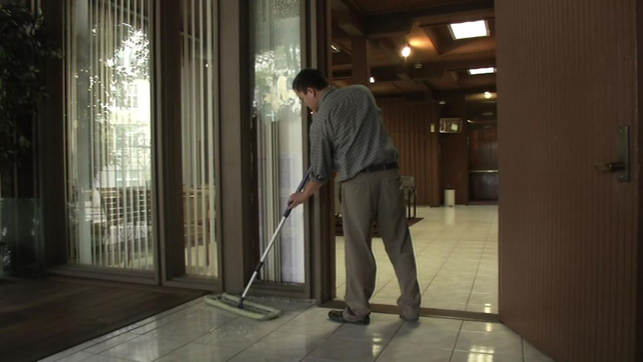 Man cleans up glass from a broken window at the Indonesian Consulate in San Francisco.