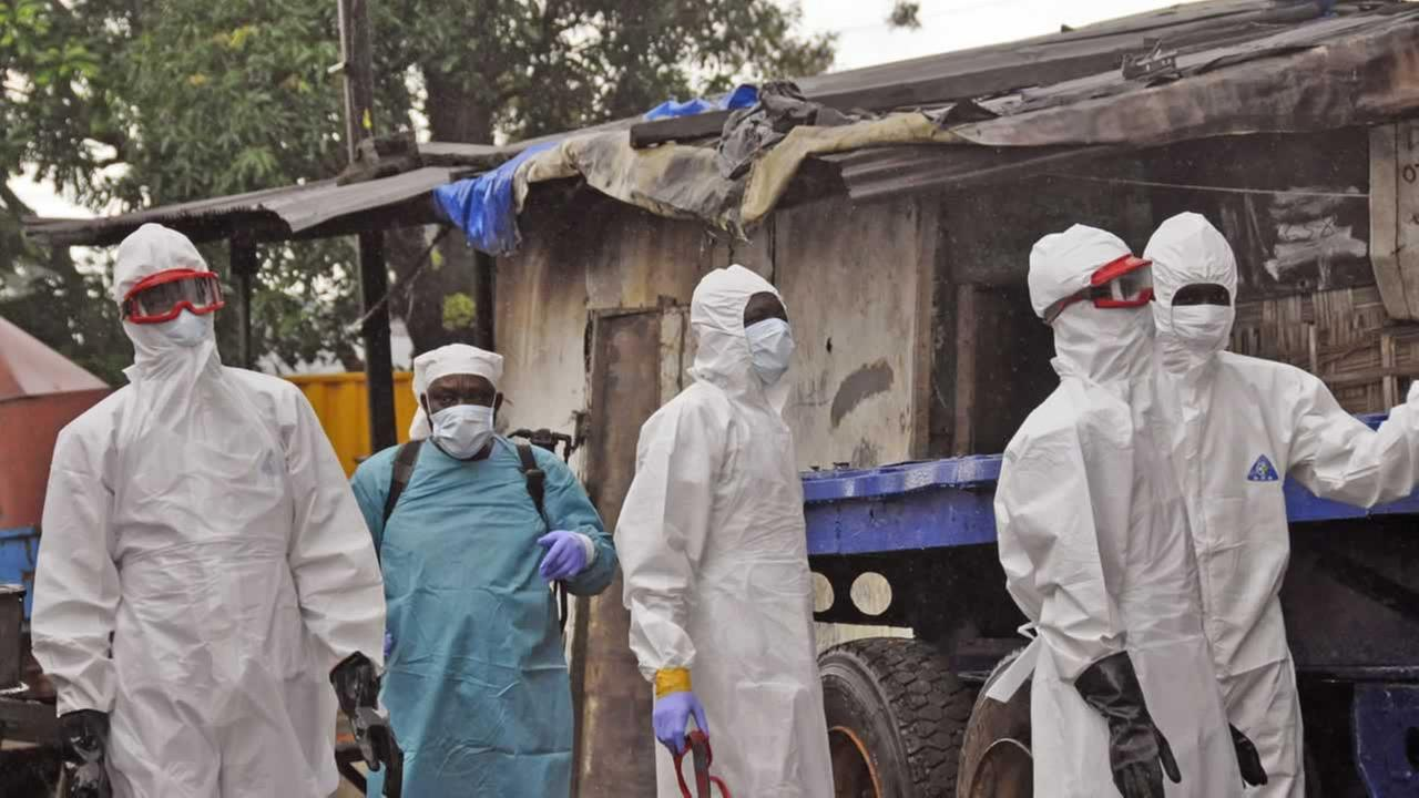 Liberian health workers outside a home of a man that they believed died from the Ebola virus in Monrovia, Liberia. (AP Photo/Abbas Dulleh)