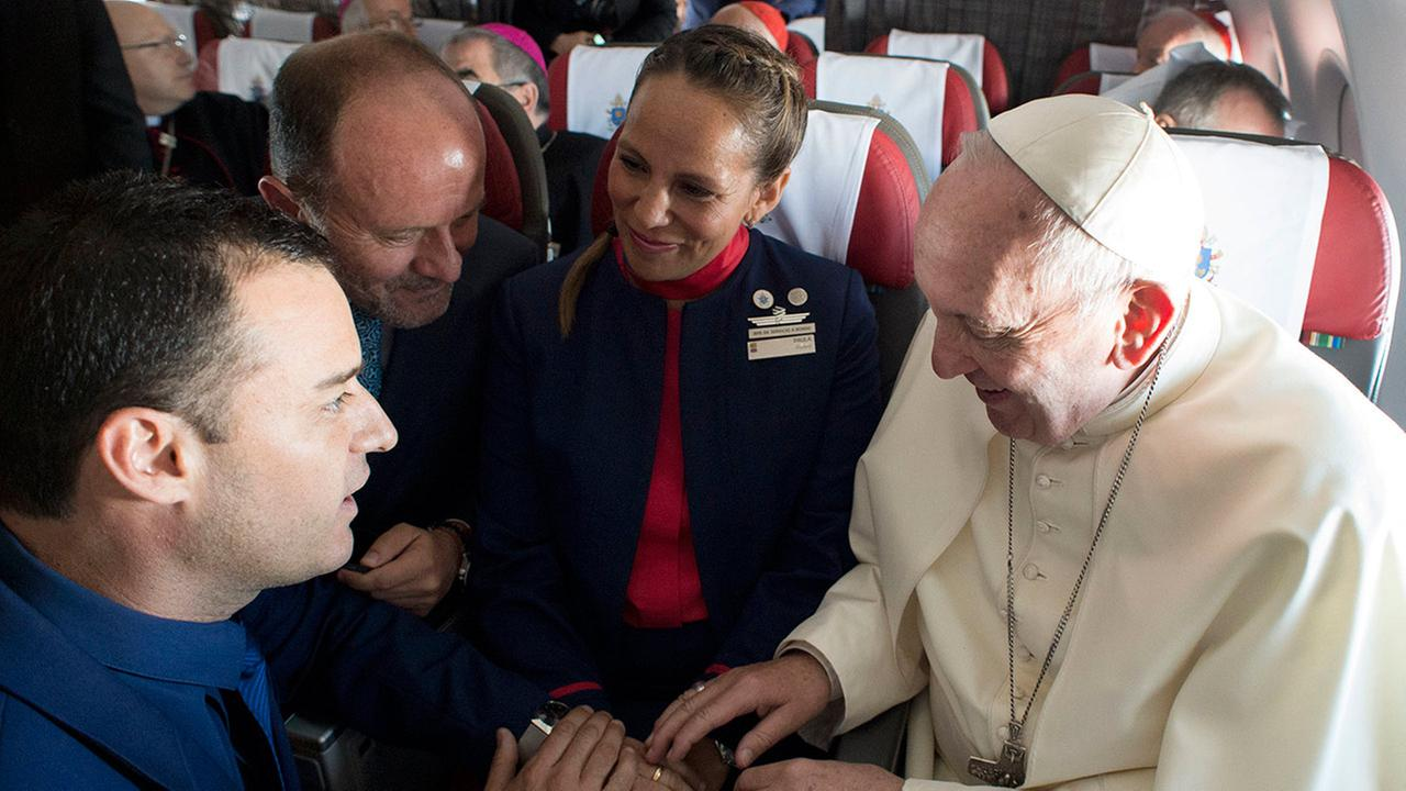 Pope Francis marries flight attendants Carlos Ciuffardi, left, and Paola Podest, center, during a flight from Santiago, Chile, to Iquique, Chile, Thursday, Jan. 18, 2018.