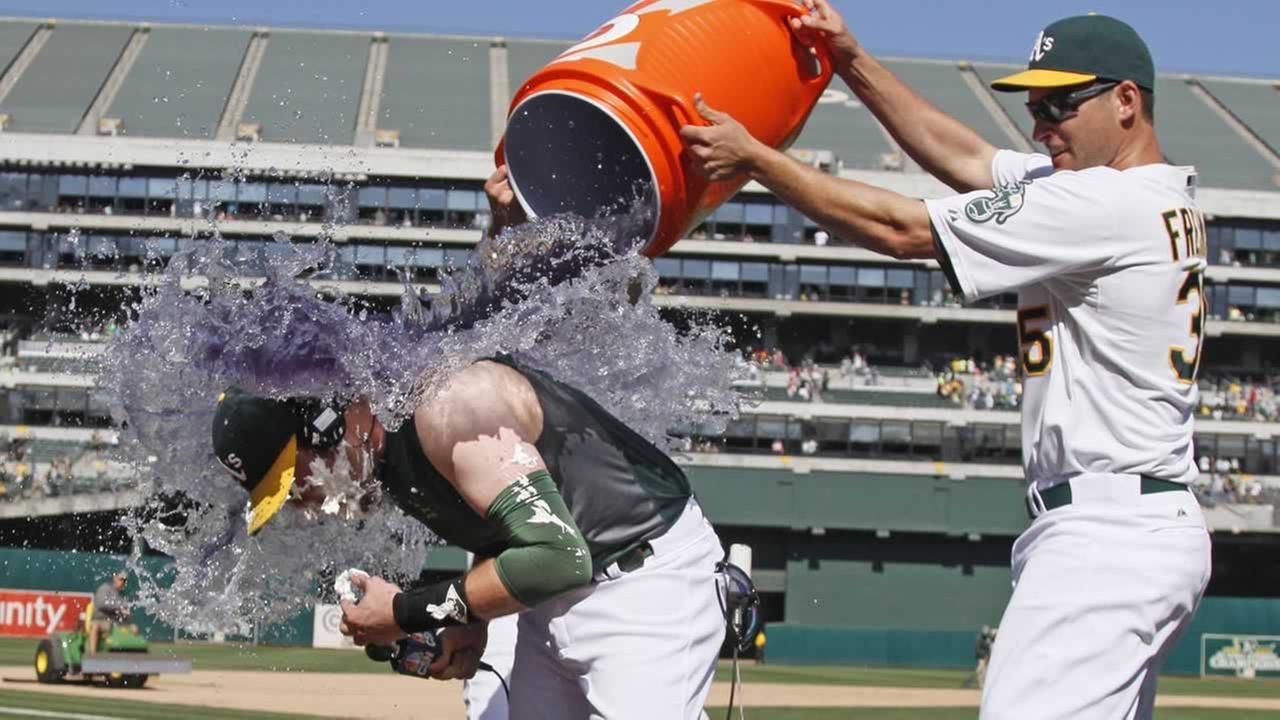 Oakland Athletics Jed Lowrie is doused by Nate Freiman during an interview at the end of their baseball game against the Houston Astros Saturday.