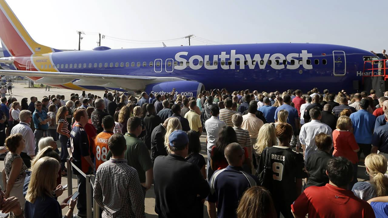 Southwest Airlines employees crowd around a newly unveiled plane paint color scheme during an event at Love Field Monday, Sept. 8, 2014, in Dallas.(AP Photo/LM Otero)