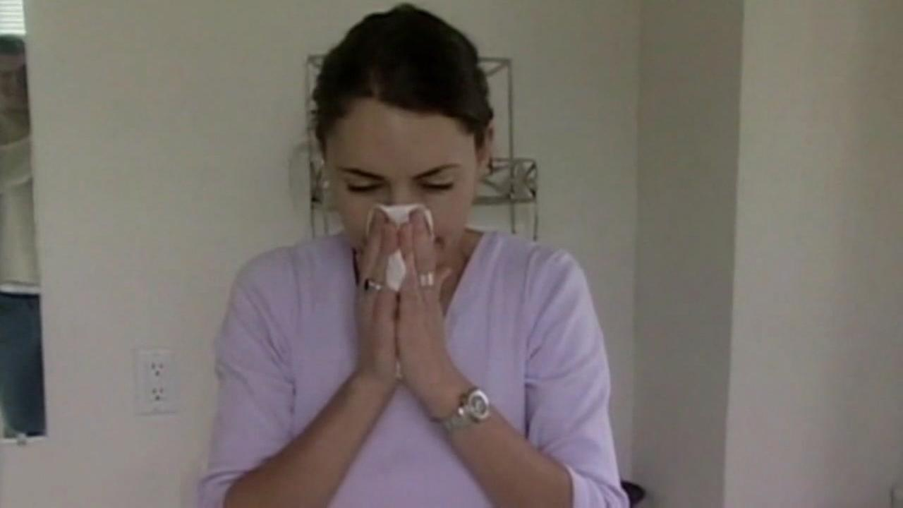 A woman sneezes into a tissue in this undated file photo.