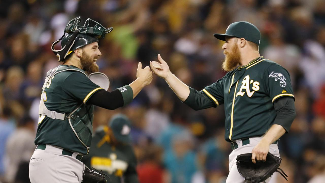 Oakland Athletics catcher Derek Norris congratulates closing pitcher Sean Doolittle after the teams 3-2 win over the Seattle Mariners in 10 innings in a baseball game Saturday.