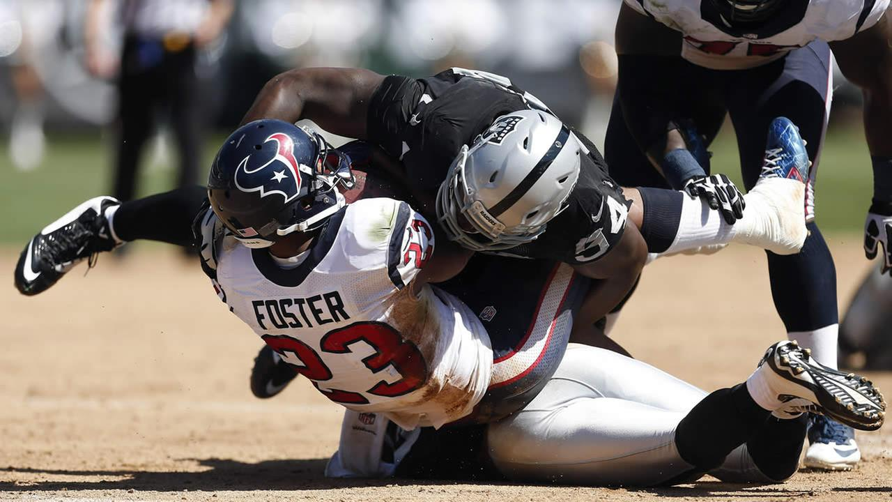 Houston Texans running back Arian Foster (23) is brought down with the ball by Oakland Raiders defensive tackle Antonio Smith in the second quarter of an NFL football game Sunday, Sept. 14, 2014, in Oakland, Calif. (AP Photo/Beck Diefenbach)